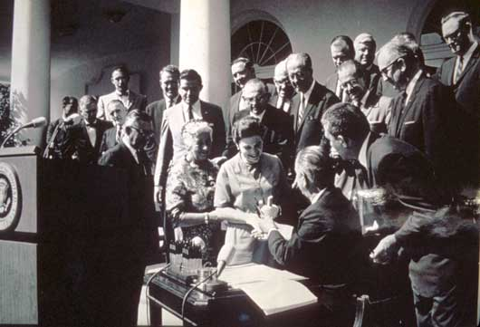 President Lyndon Johnson signs the Wilderness Act, 1964, and hands a pen to Mardy Murie. Conservationist Alice Zahniser stands between Murie and the president
