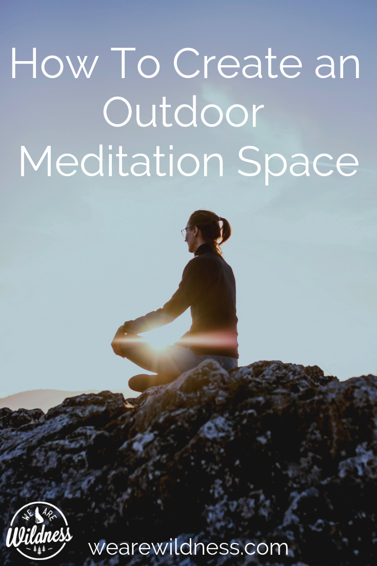 woman sitting on a boulder outside in the natural world meditating as she faces the setting sun - How To Create An Outdoor Meditation Space - We Are Wildness - mindfulness - forest bathing -